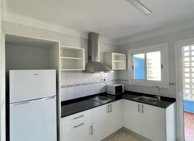 Cocina equipada con nevera y acceso a la terraza en apartamentos en Salou