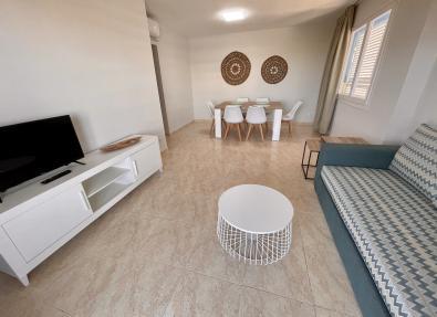 Salón con tv, sofá y zona comedor apartamentos California