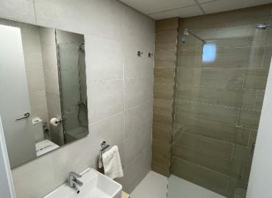 Baño con ducha con puerta de vidrio en Salou